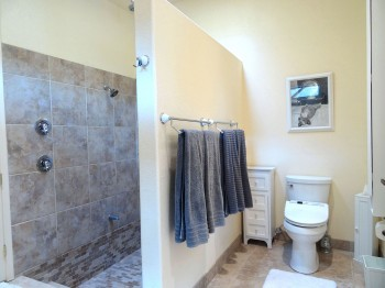 Roomy toilet area, with lots of towel racks for bath and pool towels