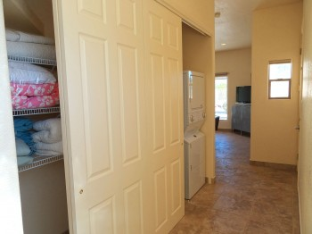 Roomy hall closet with its own hot water heater, shelving units, and stacked washer/dryer so your guests can feel at home